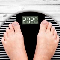 2020 feet on a weight scale on white planks, new year and holiday food nutrition and diet concept